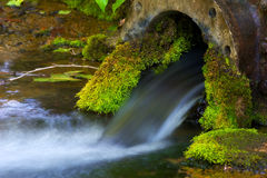 Rustic Water Pipe. An old vintage water pipe covered in moss at a spring with motion blurred water Royalty Free Stock Images