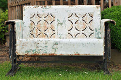 Rustic weathered bench in the grass. A metal rustic weathered bench in the grass with peeled paint and rust Stock Photography