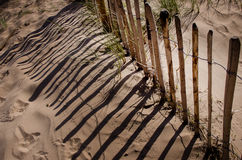 Rustic and weathered fence in front of sand dune on sandy sea beach Crosby England Europ. E Stock Image