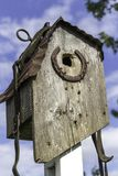 Rustic weathered wood bird house with horse shoe and leather straps. Rustic Horseshoe Bird House on a sunny day stock images