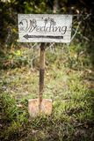 Rustic wedding arrow sign on a shovel. Homemade rustic wedding sign placed on a shovel in the woods. Arrow points right royalty free stock photography