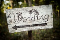 Rustic wedding arrow sign on a shovel. Homemade rustic wedding sign placed on a shovel in the woods. Arrow points right stock image