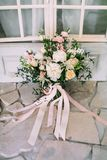 Rustic wedding bouquet with creamy roses, white carnations, and eustoma stand on the floor. Close-up. Stock Photography