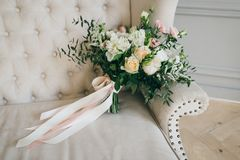 Rustic wedding bouquet with creamy roses and white carnations on a luxury cream sofa. Close-up. Side view Stock Image