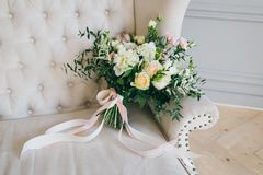 Rustic wedding bouquet with creamy roses and white carnations on a luxury cream sofa. Close-up. Side view Royalty Free Stock Photography