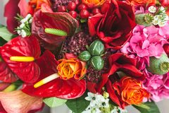 Rustic wedding bouquet with orange, crimson and bordeaux roses, poppy and other flowers and greens on wooden background Stock Photo