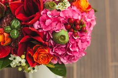 Rustic wedding bouquet with orange, crimson and bordeaux roses, poppy and other flowers and greens on wooden background Royalty Free Stock Photos