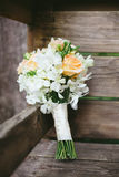 Rustic Wedding Bouquet. Pink and coral peach roses in bridal wedding bouquet leaning on a rustic wooden bench in the forest Stock Images