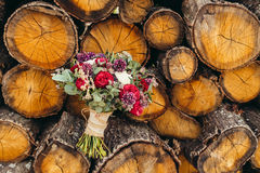 Rustic wedding bouquet with red rose and lilac flowers on wooden Stock Images