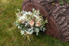 Rustic wedding bouquet with roses and other flowers on green gra Stock Image