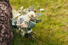 Rustic wedding bouquet with roses and succulents on green grass Royalty Free Stock Photos