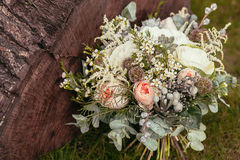 Rustic wedding bouquet with roses and succulents on green grass Royalty Free Stock Image