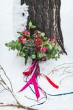Rustic wedding bouquet with succulents and crimson flowers on the snow next to the tree. Outdoors. Artwork Royalty Free Stock Images