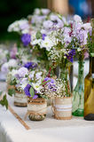 Rustic wedding decor, provence style. Lavender bouquet of field flowers and glass spice jars on wooden table Royalty Free Stock Photography