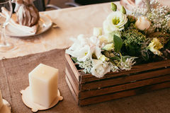 Rustic wedding decorations. wooden box and candle with bouquet o Stock Images