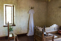 Rustic wedding dress hanging on the chandelier in the room Royalty Free Stock Photography