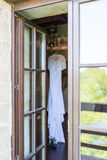 Rustic wedding dress hanging on the chandelier in the room Stock Photo