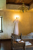 Rustic wedding dress hanging on the chandelier in the room Stock Photos