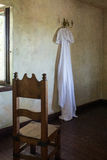 Rustic wedding dress hanging on the chandelier in the room Royalty Free Stock Images