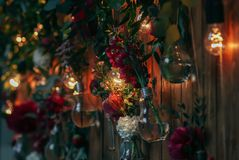 Rustic wedding photo zone. Hand made wedding decorations includes Photo Booth  red flowers. Garlands and light bulbs Stock Image