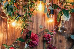 Rustic wedding photo zone. Hand made wedding decorations includes Photo Booth  red flowers. Garlands and light bulbs Stock Images