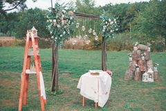 Rustic wedding photo zone. Hand made wedding decorations includes Photo Booth, wooden barrels and boxes, lanterns, suitcases and. White flowers Stock Photography