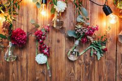 Rustic wedding photo zone. Hand made wedding decorations includes Photo Booth  red flowers. Garlands and light bulbs Royalty Free Stock Photos