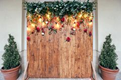 Rustic wedding photo zone. Hand made wedding decorations includes Photo Booth  red flowers. Garlands and light bulbs Royalty Free Stock Images