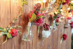 Rustic wedding photo zone. Hand made wedding decorations includes Photo Booth  red flowers. Garlands and light bulbs Stock Photos