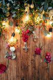 Rustic wedding photo zone. Hand made wedding decorations includes Photo Booth  red flowers. Garlands and light bulbs Stock Photography
