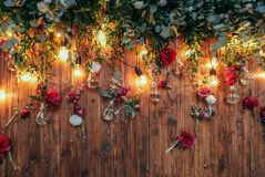 Rustic wedding photo zone. Hand made wedding decorations includes Photo Booth red flowers. Garlands and light bulbs stock photo