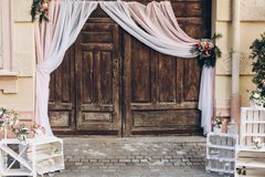 Rustic wedding photo zone. wooden barn doors with fabric and white boxes with flowers and candles at stylish wedding photo booth. Shabby chic. luxury stock photos