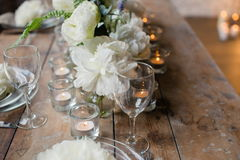 Rustic wedding table. Nice rustic wedding table decorated with beautiful white David Austin roses and candles in glass holders. Rare romantic flowers on plates Stock Image