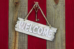 Rustic welcome sign with skeleton key. Wood welcome sign with brass skeleton key hanging on antique red and wooden rustic background Stock Image