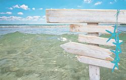 Rustic white empty wood signs with turquoise starfish over fresh green ocean water. At Es Trenc, Mallorca Royalty Free Stock Photos