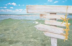 Rustic white empty wood signs with yellow starfish. Over fresh green ocean water at Es Trenc, Mallorca Royalty Free Stock Photos