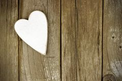 Rustic white wooden heart on aged wood background Stock Photo