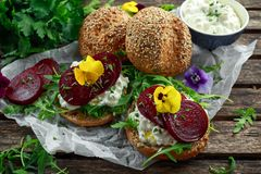 Rustic wholegrain buns with cottage cheese, rocket leaves, beetroot slices and edible viola flowers. Vegetarian food. Snack stock photography