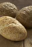 Rustic wholegrain loaves. On a wooden bread board stock image