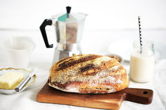 Rustic wholegrain sourdough loaf, butter, almond milk, coffee Stock Images