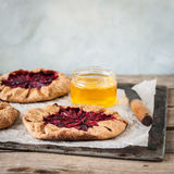 Wholemeal Plum Galettes with Honey. Rustic Wholemeal and Brown Sugar Plum Galettes with Honey, copy space for your text, square Royalty Free Stock Photos