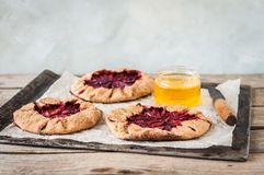 Wholemeal Plum Galettes with Honey. Rustic Wholemeal and Brown Sugar Plum Galettes with Honey, copy space for your text Royalty Free Stock Photo