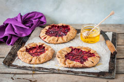 Wholemeal Plum Galettes with Honey. Rustic Wholemeal and Brown Sugar Plum Galettes with Honey, copy space for your text Royalty Free Stock Photography