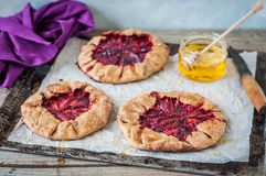 Wholemeal Plum Galettes with Honey. Rustic Wholemeal and Brown Sugar Plum Galettes with Honey Royalty Free Stock Images