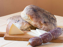 Rustic wholesome produce - bread, salami and cheese. Royalty Free Stock Photography