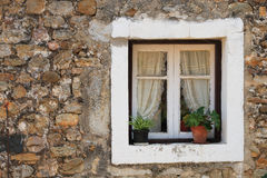 Rustic window. Detail of stone wall and window of country house Stock Image
