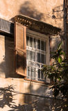 Rustic window. An old rustic window in a home located in Beirut, Lebanon, with a loquat fruit tree growing outside casting shadows on the wall Royalty Free Stock Image