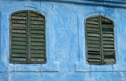Rustic windows. Rustic green window shutters on blue wall in Transylvania Stock Photography