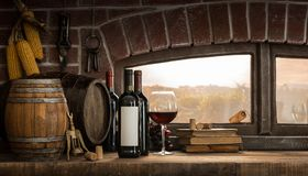 Rustic wine cellar in the countryside. Wine glasses, bottles and barrels in a rustic countryside wine cellar; panoramic window view of lush vineyards at sunset royalty free stock photography