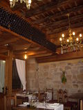 Rustic wine restaurant. Rustic cellar restaurant in the north of Spain with old fashioned golden chandeliers, stone walls and wine bottles royalty free stock photography
